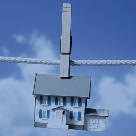 Symbolic house on clothes line --- Image by © Mike Kemp/Tetra Images/Corbis